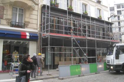 Disassembling the scaffolding reveals the new dark facade at our Paris café