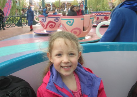 Smiling at Grandad as they share a spinning teacup at Paris Disney