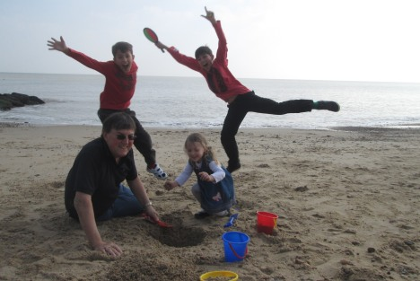 Clive and his grandchildren on the beach in Felixstowe